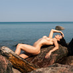 Nude woman lying on stones — Stock Photo