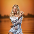 Sexy blonde woman in water at sunset .Beautiful swimsuit model in the water - Stock Photo